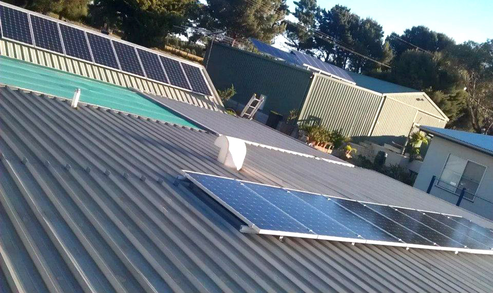 Flat and angled solar panels across shed roofs